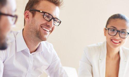 Trois employés de bureau en réunion sourient